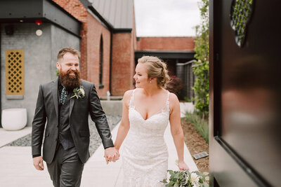 wedding couple walking hand in  hand at their clementine nashville wedding
