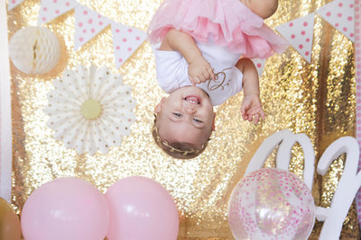 A one year old girl hoisted above laughs in Wauchula, Florida.