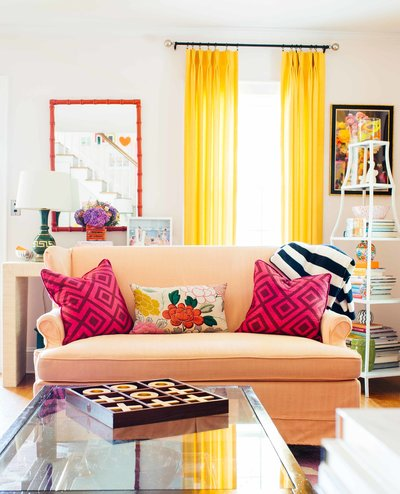 A peach sofa with bright pillows in colorfully decorated living room.