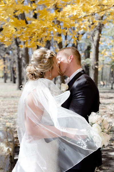 Fall wedding where Bride and Groom share a kiss while veil is swept over them