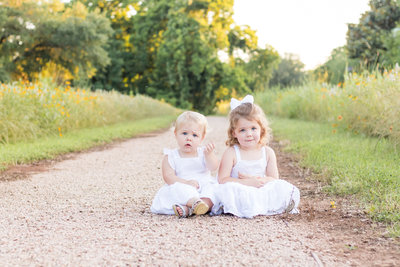 sweet sisters sitting side by side on a pathway