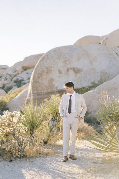groom in beige suit standing with his hands in his pockets in the joshua tree desert