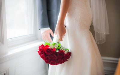 Bride and Groom in Ajax holding boquet. The photo is cut around the wasite to the lower legs to emphasize the beautiful boquet, some bright red roses.