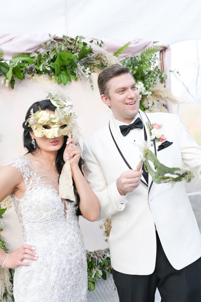Bride and groom hold decorative masks