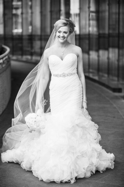 An editorial photo of a bride is walking while holding her bouquet down with her right hand and not looking at the camera.