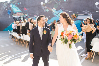Bride and groom smile at each other brightly after getting married