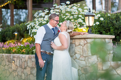 Bride and Groom laughing by the flowers at Lake Oak Meadows wedding venue