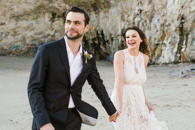 A happy wedding couple runs on the beach at Shark Fin Cove in California.