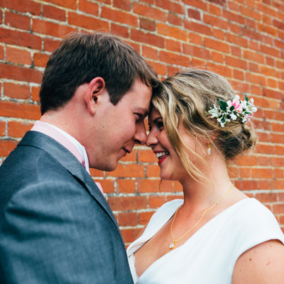 Intimate natural bride and groom wedding portrait in Suffolk against brick wall