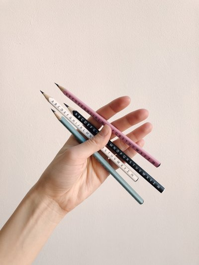 photo-of-person-holding-assorted-pencils-1029793
