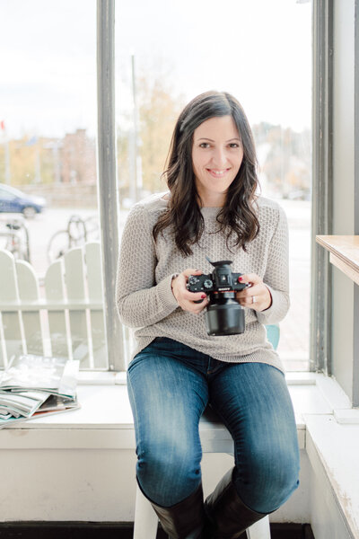 woman smiling and holding camera