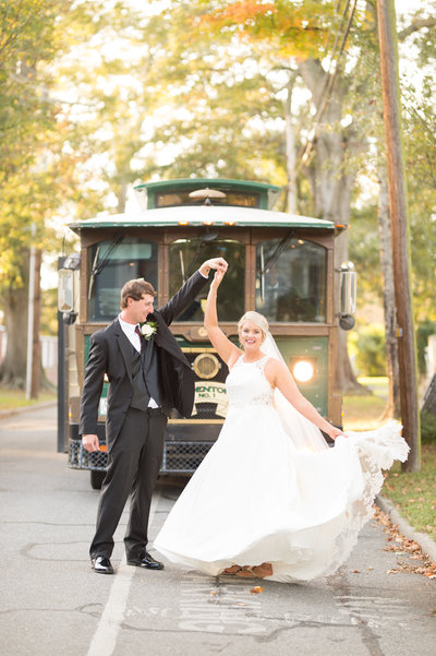 Bride and groom standing in front of a trolly
