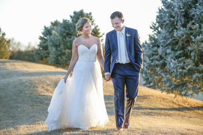 Couple walk outside of Wilderness Ridge Golf Club before their wedding