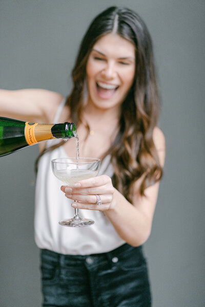 woman poring champagne into a glass for a toast