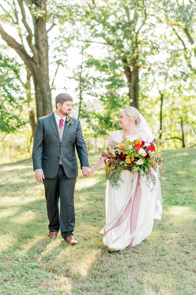 Couple walking with loose fall bouquet at their family estate wedding