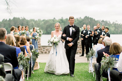 Bride and Groom smiling walking down aisle together