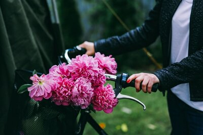 Woman holding a bike with beautiful pink flowers in the basket