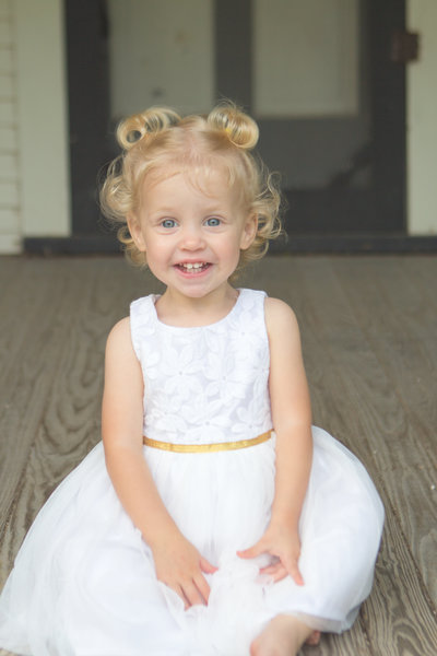 Blonde Toddler Girl in White Dress Smiling