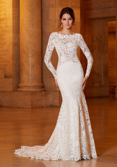 Exquisite allover Venice Lace takes center stage on the stunning Alexandria designer wedding dress. Luxurious long sleeves and a breathtaking open back perfectly complement the fit to flare silhouette. A scalloped hemline and sheer train complete the look.