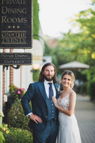 Couple standing and smiling in front of Inn on the Twenty Sign