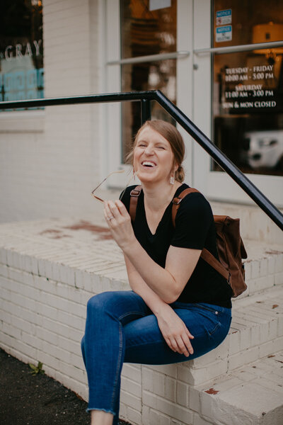 copywriter diana p. carter  laughing on white steps in charlotte, nc