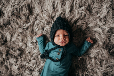 newborn baby boy laying on rug with bonnet on