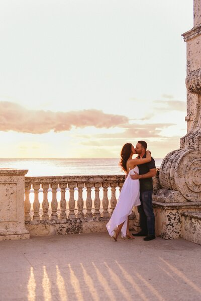 man and woman kissing on balcony in front of ocean