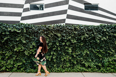 woman walking with ivy wall and mural