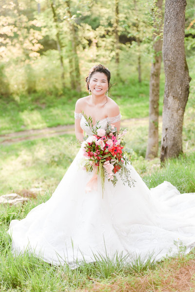 Bride smiles bright while holding colorful bouquet on a lawn