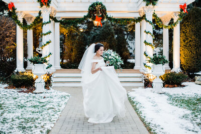 bride with the flowers walking around  gazebo behind  on the snowy day