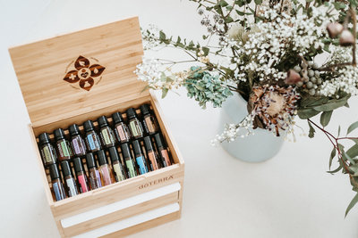 doTERRA essnetial ois in a wooden box sitting on a countertop with vase of flowers