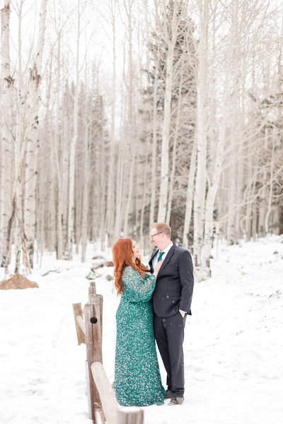 A redhead in a green dress during an engagement session in the snow