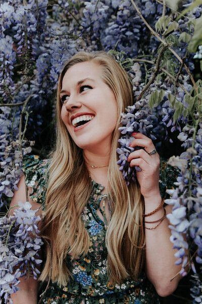 woman smiling while surrounded by purple flowers