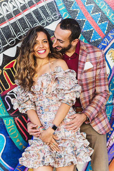 brightly colored engagement photography with couple in front of building in the Mission District, San Francisco