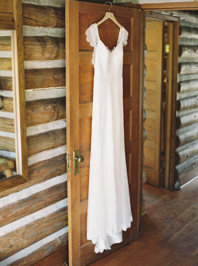 Wedding dress hanging in 320 Ranch in Big Sky, Montana by Orange Photographie
