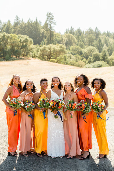 Bride with her orange and yellow bridesmaids posing  in field in Yountville, California. Photo taken by Cheers Babe Photo.