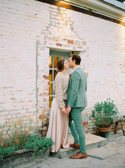 Stolen kiss between a bride and groom with a blush gown and wheat sweater and a light green wool suit