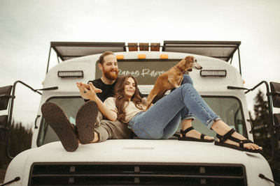 man and woman sitting on jeep hood
