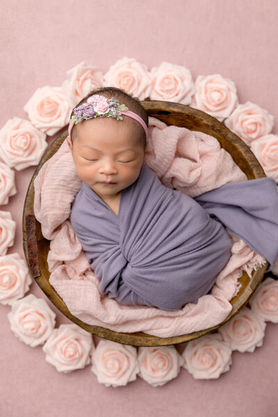 newborn girl swaddled in purple on a pink background with flowers