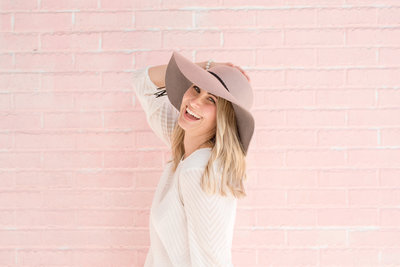 Photographer Amanda Zabrocki smiles against a pink brick wall in hat and white blouse