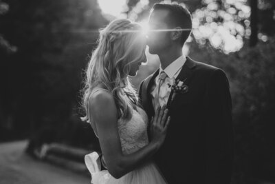 Groom kissing bride on the forehead at outdoor oak glen wedding venue