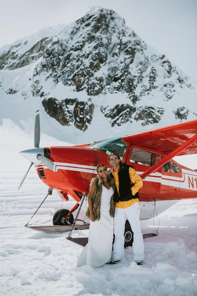 bride and room standing in front of a red plane in the mountains after their Alaska Elopement