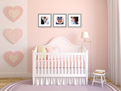 framed newborn portraits hanging over crib in baby room