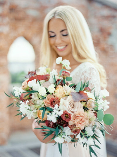 Smiling bride in lace dress posing with her bridal bouquet