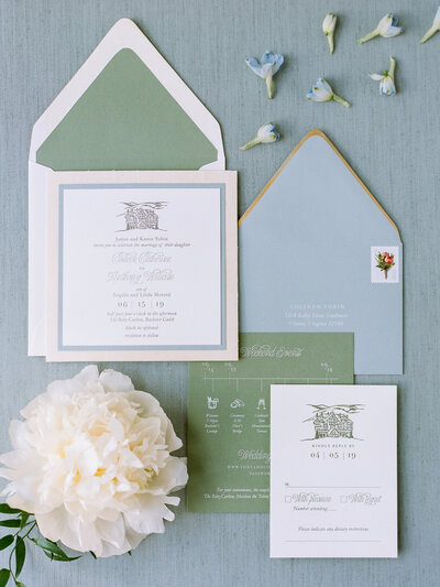 Flat-lay of green, white, and blue wedding stationery, small blue flowers surround the paper