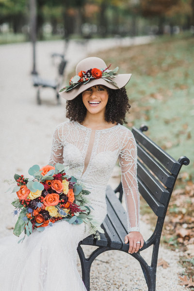 bride with autumn flowers orange red blue yellow green on park bench