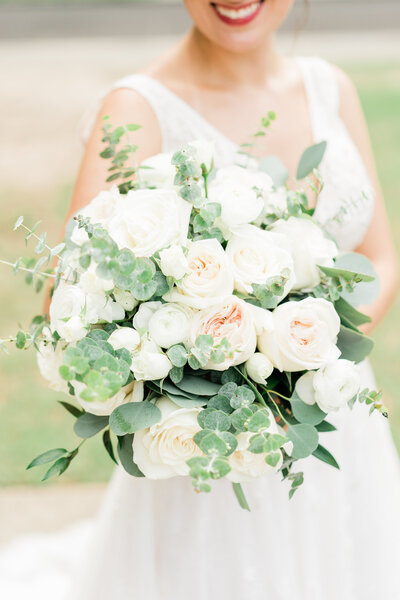 Closeup of bridal bouquet in Alabama with white roses and green accents