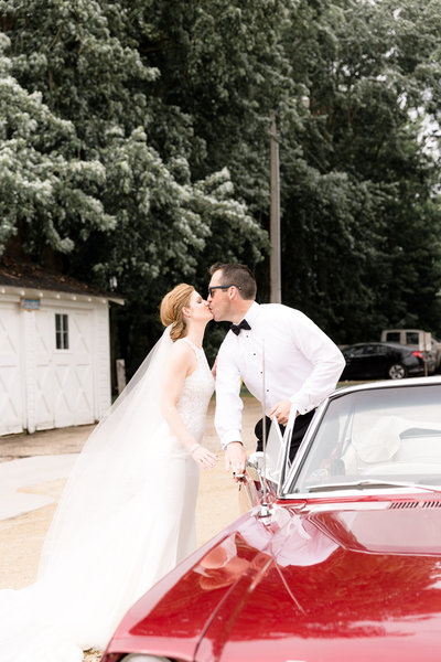 Bride and Groom sharing a kiss after Bride surprised her husband with a classic red convertible car for their getaway