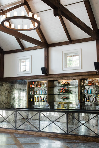 Beautiful bar within wedding venue with mirrored finishes and high ceilings complete with wooden beams