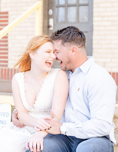 Happy fiances laughing during engagement photos